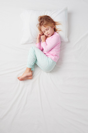 bed time: Top view photo of little girl sleeping on white bed.