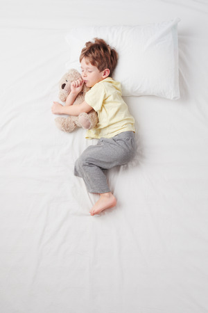 Top view photo of little cute boy sleeping on white bed with teddy bear. Standard-Bild