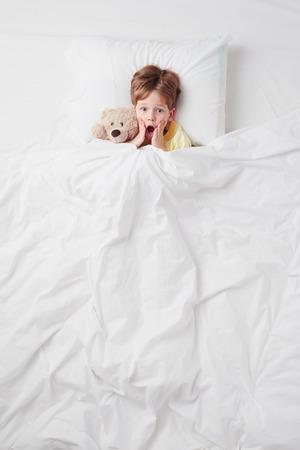 Bovenaanzicht foto van kleine bang jongen onder deken met teddybeer.