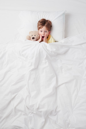 bed time: Top view photo of little scared boy under blanket with teddy bear. Stock Photo