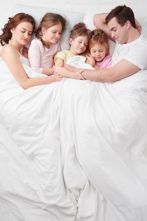 白いベッドの上の毛布の下で 5 人家族の上面写真。 写真素材