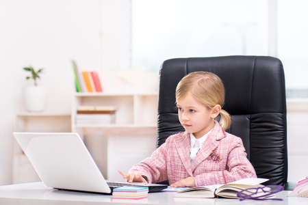 Funny picture of little cute girl playing role of business woman. Girl wearing pink suit. Girl sitting at table on large office chair and using laptop. Office interior as a background