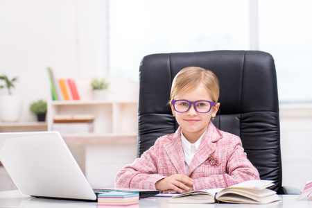 Funny picture of little cute girl playing role of business woman. Girl wearing pink suit and glasses. Girl sitting at table on large office chair, smiling and looking at camera. Office interior as a background