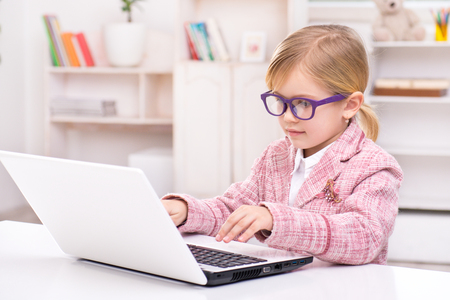 Funny picture of little cute girl playing role of business woman. Girl wearing pink suit and glasses. Girl sitting at table and using laptop. Office interior as a background