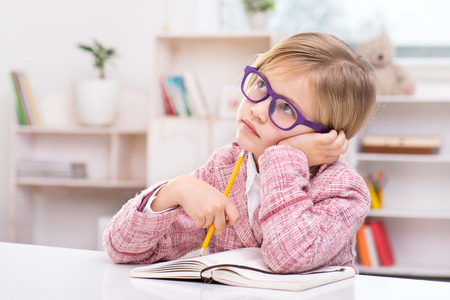 Funny picture of little cute girl playing role of business woman. Girl wearing pink suit and glasses. Girl thoughtfully sitting at table with notebook and holding pencil. Office interior as a backgrou