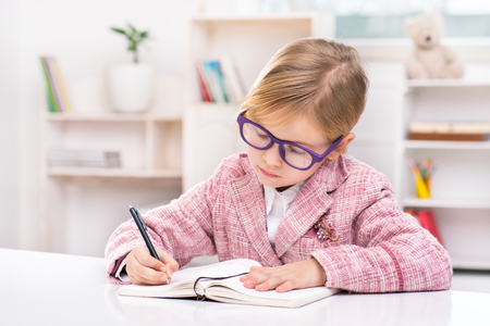 Funny picture of little cute girl playing role of business woman. Girl wearing pink suit and glasses. Girl sitting at table and adding something to bookmark. Office interior as a background