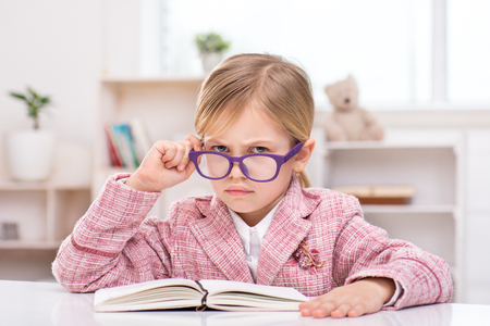 Funny picture of little cute girl playing role of business woman. Girl wearing pink suit and glasses. Girl sitting at table with notebook and sadly looking at camera. Office interior as a background