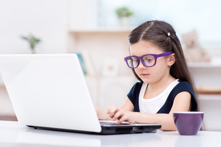 Funny picture of little dark-haired girl playing role of business woman. Girl wearing glasses. Girl sitting at table with cup and using laptop. Office interior as a background