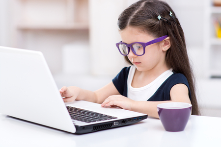 Funny picture of little dark-haired girl playing role of business woman. Girl wearing glasses. Girl sitting at table and using laptop. Office interior as a background 写真素材