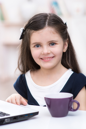 Nice picture of little dark-haired girl. Girl sitting at table with cup and laptop, smiling and looking at camera. Room interior as a background