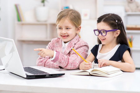 Funny picture of two little cute girls playing role of business women. Girls sitting at table with book and cheerfully looking at laptop. Office interior as a background