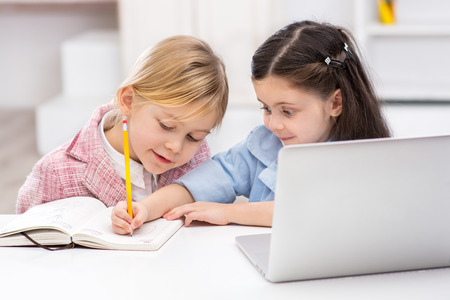 Funny picture of two little cute girls playing role of business women. Girls sitting at table with laptop and drawing. Office interior as a background