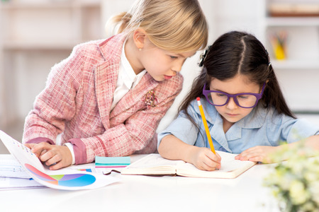 Funny picture of two little cute girls playing role of business women. Girls sitting at table with graphs and drawing. Office interior as a background