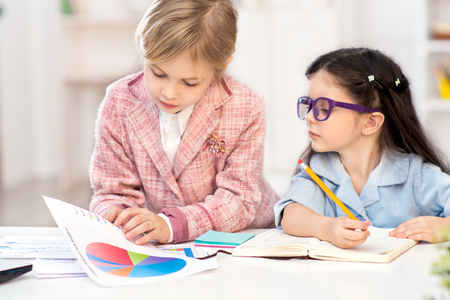 Funny picture of two little cute girls playing role of business women. Girls sitting at table, looking at graphs and drawing. Office interior as a background