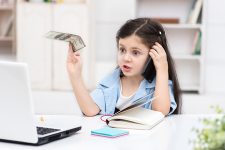 Funny picture of little dark-haired girl playing role of business woman. Girl sitting at table, holding one hundred dollars and using phone. Office interior as a background