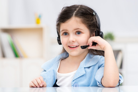 Funny picture of little dark-haired girl playing role of business woman. Girl sitting at table with headphone. Office interior as a background. Concept for call centre