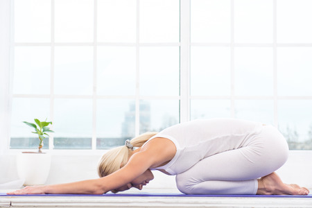 Nice photo of beautiful woman practicing yoga. Woman meditating with her eyes closed while doing childs pose. White interior with large window Stock Photo