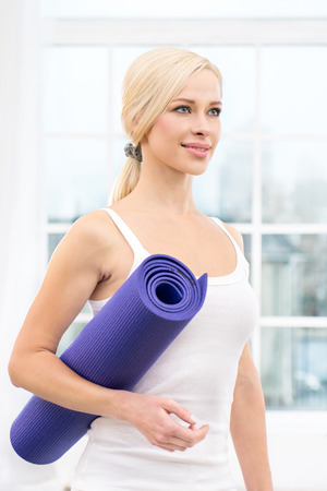 yoga mat: Close up photo of beautiful sporty woman. Woman holding violet fitness mat and smiling. White interior with large window Stock Photo