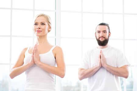 Nice photo of young woman and man practicing yoga. They meditating while doing lotus pose. White interior with large window. Focus on woman
