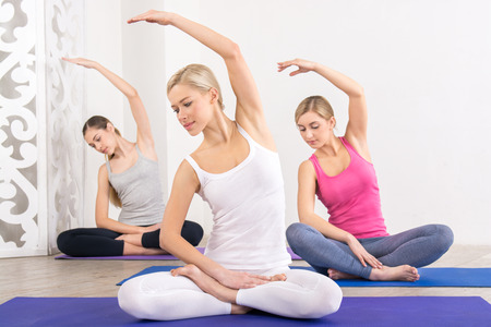 Nice photo of young three women practicing yoga. Women doing lotus pose on fitness mats. White interior Stock Photo