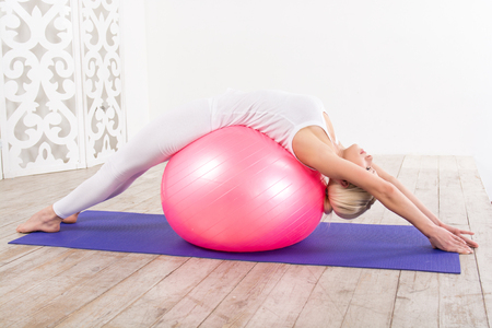 Nice photo of beautiful sporty woman. Woman doing exercises on violet fitness mat with her back on pink fitness ball. White interior