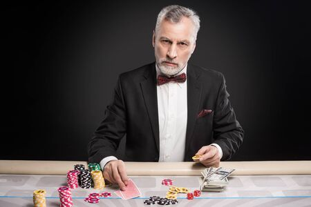 hope indoors luck: Man in years sitting at poker table, playing poker and looking seriously at camera. The chips and money are on table