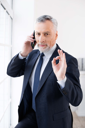 Businessman in years standing near large window, using mobile phone, looking at camera and showing ok sign