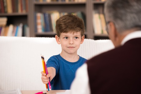 Little boy talking with psychologist. Focus on boy. Boy giving crayons to psychologist. There are many books in psychologist office Stock Photo