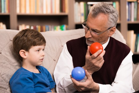 medical therapy: Little boy talking with psychologist. Boy choosing between red and blue balls. There are many books in psychologist office