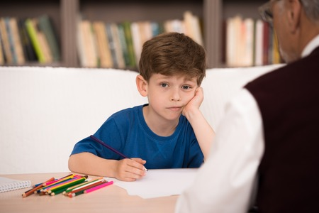 health service: Sad little boy trying to draw in psychologist office. Focus on boy. There are many books in psychologist office Stock Photo