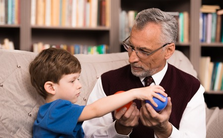 man health: Little boy talking with psychologist. Boy choosing blue between two balls. There are many books in psychologist office