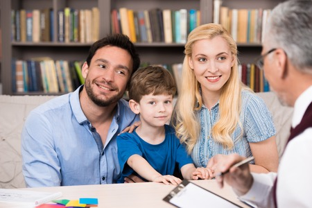 Young family of three talking with psychologist. Psychologist taking notes. There are many books in psychologist office Stockfoto