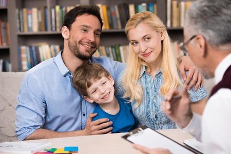 Glückliche Familie von drei Gespräche mit Psychologen. Psychologe Notizen. Es gibt viele Bücher in Psychologin Büro