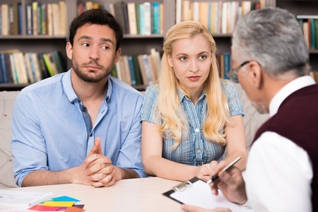 mental illness: Young nervous couple talking with psychologist. Psychologist taking notes and explaining something to them. There are many books in psychologist office