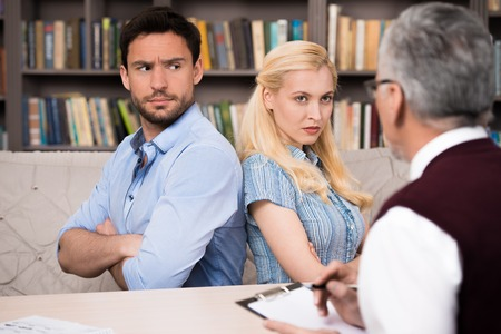 medical man: Young couple talking with psychologist. Psychologist taking notes. Angry man and woman sitting back to back. There are many books in psychologist office Stock Photo