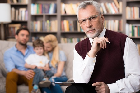 Young family talking with psychologist. Focus on psychologist. There are many books in psychologist office Stock Photo