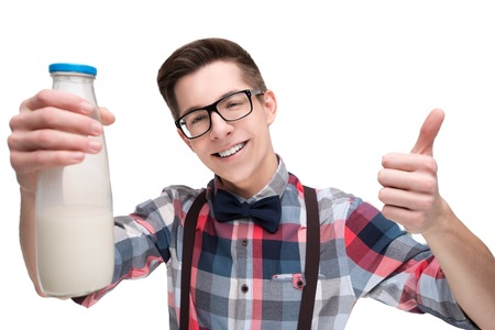 nerd: Young nerd in glasses and checkered shirt with bottle of milk gesturing thumb up isolated on white background Stock Photo