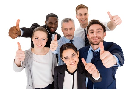 Multi-ethnic business team standing isolated on white, looking up, smiling and showing thumbs up to camera Stock Photo