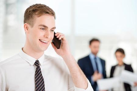 personas comunicandose: Hombre de negocios sonriente joven que usa el teléfono móvil y mirando a un lado. La gente de negocios que se comunican en el fondo
