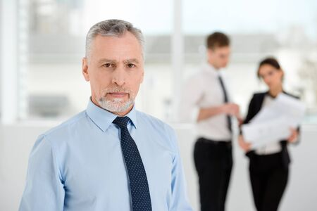 people communicating: Aged businessman looking at camera. Business people communicating in the background