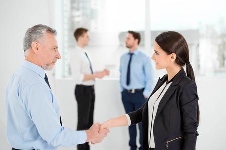 personas comunicandose: Empresario de edad y j�venes empresaria dar la mano. La gente de negocios que se comunican en el fondo