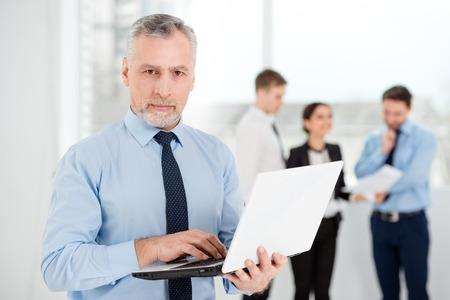 personas comunicandose: Empresario de edad usando la computadora portátil blanco y mirando a la cámara. La gente de negocios que se comunican en el fondo Foto de archivo