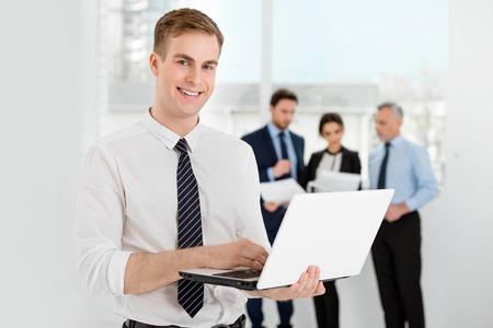 personas comunicandose: Hombre de negocios sonriente joven que usa el ordenador port�til y mirando a la c�mara. La gente de negocios que se comunican en el fondo
