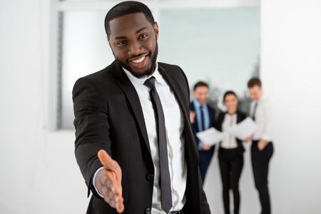 personas comunicandose: Empresario estadounidense sonriente joven que mira la cámara y alcanzar hacia fuera su mano. La gente de negocios que se comunican en el fondo