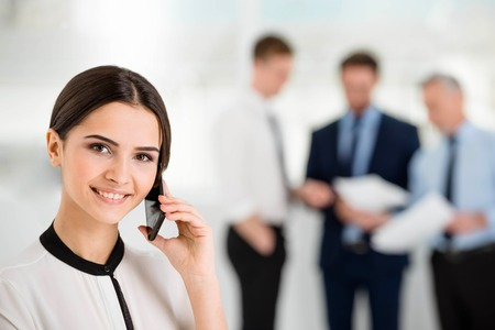 Young smiling businesswoman looking at camera and using mobile phone. Businessmen communicating in the background Standard-Bild