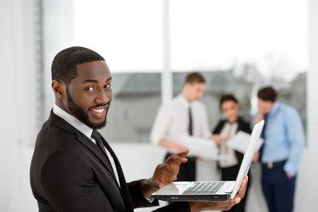 personas comunicandose: Empresario estadounidense sonriente joven que mira la cámara y computadora portátil. La gente de negocios que se comunican en el fondo Foto de archivo