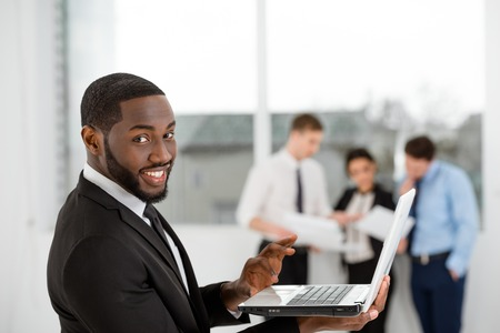 people communicating: Young smiling African-american businessman looking at camera and using laptop. Business people communicating in the background Stock Photo