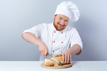 Portrait of positive young male chef in white uniform. Head-cook looking at camera and slicing freshly baked bread. Sitting against grey background