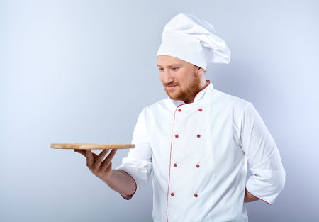 Portrait of positive young male chef in white uniform. Head-cook holding wooden board for cutting and looking at it. Standing against grey background