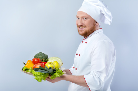 Side view photo of positive young male chef in white uniform. Head-cook cheerfully smiling, looking at camera and holding big plate of fresh vegetables. Standing against grey background Фото со стока